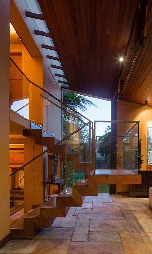 A escada em balanço é feita de madeira e tem guarda-corpo de vidro. A circulação recebe iluminação natural tanto pelas aberturas laterais, quanto pela claraboia que forma uma faixa contínua no teto. A casa Várzea foi projetada pelo arquiteto Gustavo Penna