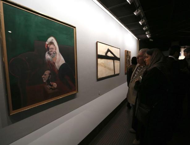 20.nov.2015 - Visitantes observam obra de Francis Bacon exposta em Teerã - ATTA KENARE/AFP