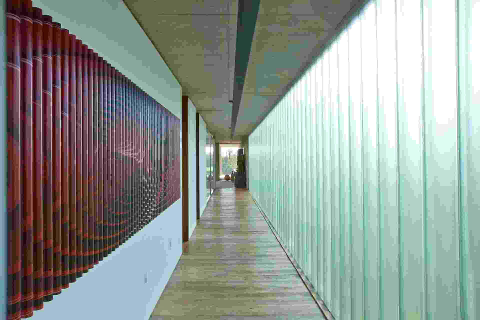 De um lado do corredor está o paredão composto por um sistema de envidraçamento (Pilkington), que permite a entrada máxima de luz natural. Do outro, os arquitetos Alice Martins e Flavio Butti dispuseram uma obra de arte que deixa o caminho mais dinâmico e agradável - Luis Gomes/Divulgação