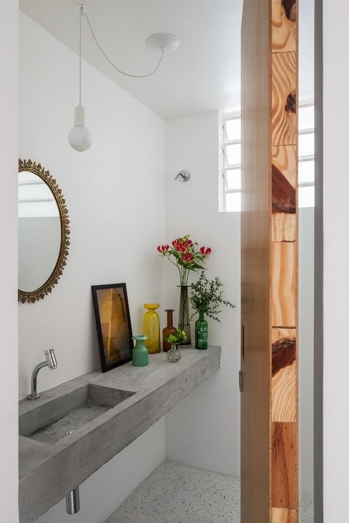 O lavabo do apê 62, em São Paulo, conta com uma bancada de concreto com pia embutida. A decoração ganha delicadeza com o uso de garrafas e vasos de tamanhos diversos, bem como do espelho com moldura rebuscada