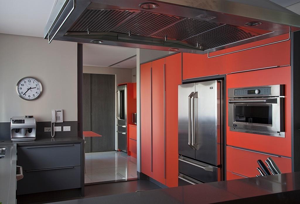 A cozinha desse apartamento em São Paulo foi concebida pela arquiteta Consuelo Jorge e chama a atenção pelos armários com portas de vidro laranja combinados a revestimentos cinzas e a eletrodomésticos em aço inox