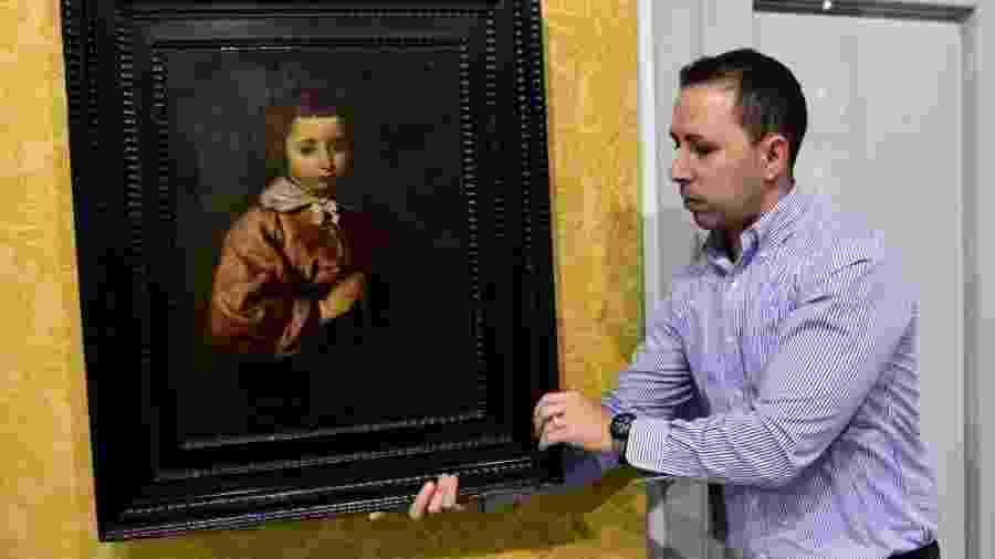 Funcionário da galeria Abalarte manuseia quadro de Diego Velázquez  - Gerard Julien/AFP Photo