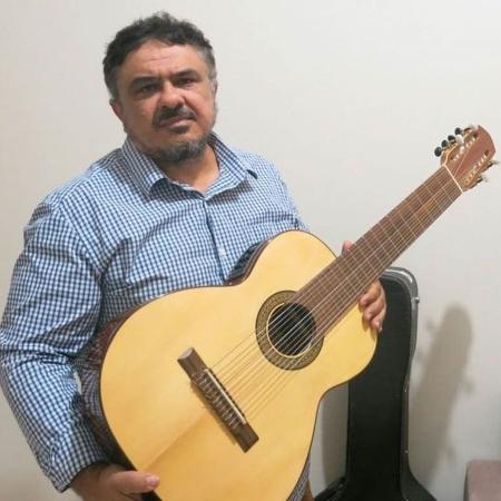 Reinaldo Casteluzzo com sua invenção: um violão de 12 cordas, que pode ser tocado com uma só mão - BBC