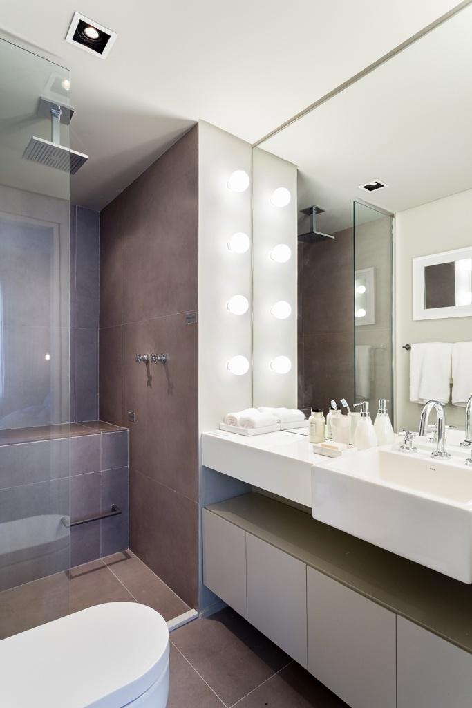 No banheiro do casal, os revestimetos em porcelanato e a marcenaria são em tons de cinza. Para conseguir um ar glamouroso, o espelho ganhou soquetes laterais para lâmpadas-pêra, em estilo camarim. O chuveiro de teto, além das demais louças e metais são Deca. Como não conta com janelas, o banheiro tem exaustor embutido no rebaixo de gesso, assim como a iluminação direta. O apartamento Alvorada é um projeto do escritório Suite Arquitetos