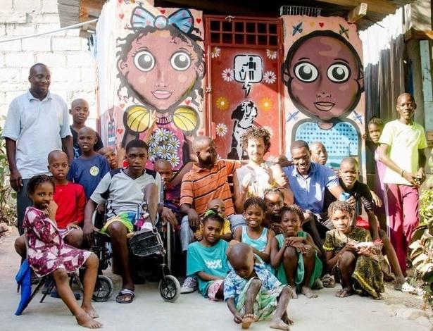 Ricardo Tatoo (ao centro) posa com grafite e crianças de orfanato em Porto Príncipe - Bruno Santos/Divulgação