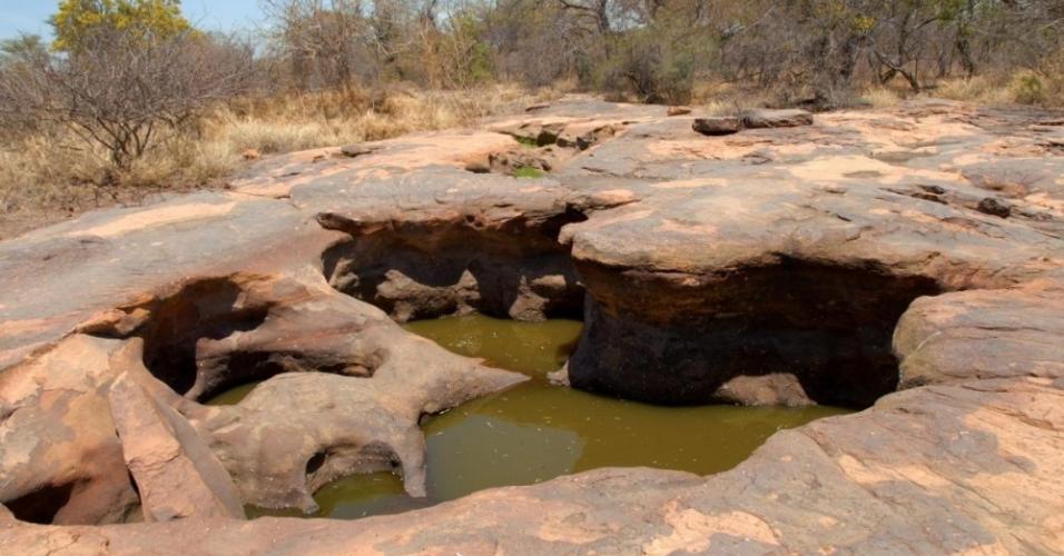 """Chamado de """"as pegadas de Matsieng"""", esse monumento nacional é na verdade uma área de rocha com dois buracos profundos. A lenda diz que um gigante de uma perna só saiu de um desses buracos, seguido de seu povo, dando origem ao povo do país."""