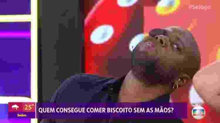 Érico Brás com batom na boca e biscoito no olho durante prenda no Se Joga de hoje - Reprodução/Globo