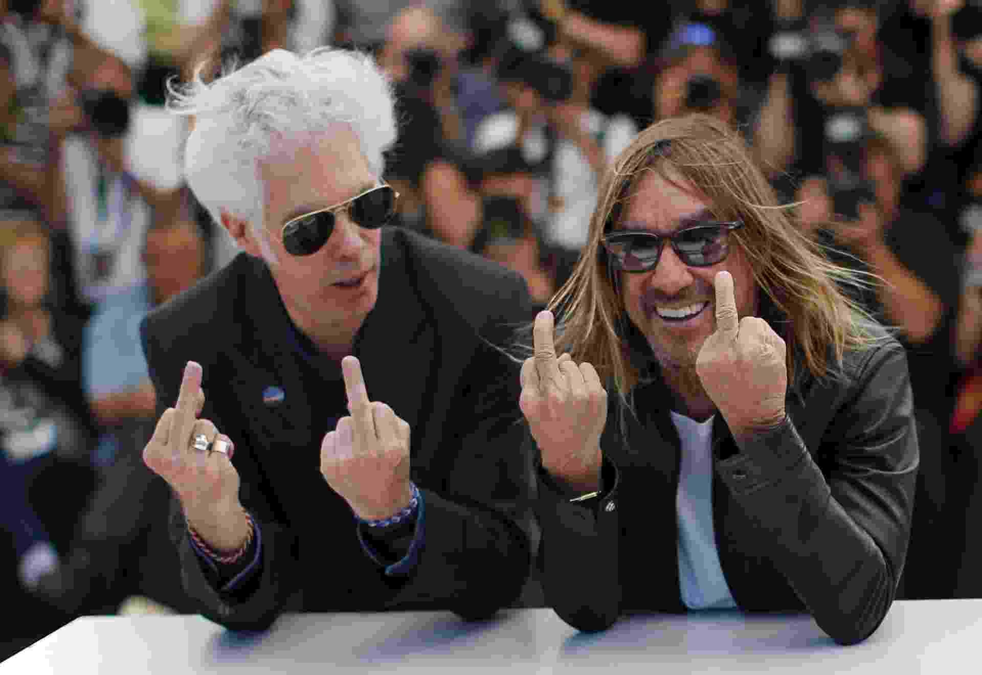 19.mai.2016 - Diretor Jim Jarmusch e cantor Iggy Pop mostram o dedo do meio no tapete vermelho de Cannes - REUTERS/Eric Gaillard