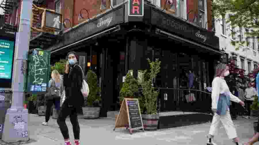 Nova-iorquinos passam por bar protegidos por máscaras - Getty Images