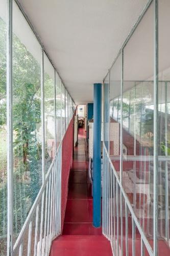 Do alto da escada que liga o térreo ao mezanino, onde está o estúdio, é possível visualizar o extenso corredor que percorre os ambientes sociais (estar com lareira e jantar), além de cozinha, banheiros e, ao fundo, um dos dormitórios. Os fechamentos em vidro garantem a transparência necessária para entrada de luz natural e integração com o exterior. A Casa do Arquiteto foi projetada por João Batista Vilanova Artigas, em 1949