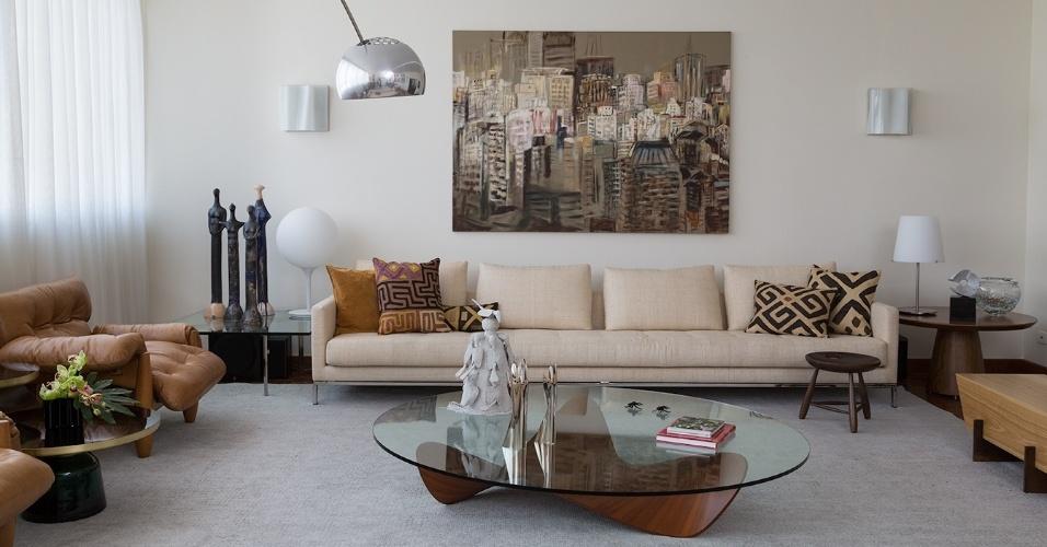 A pintura a óleo sobre tela, de Alex Orsetti, retrata edifícios de São Paulo. Com o quadro centralizado na parede de fundo do sofá, a composição do ambiente não ofusca a obra, já que predominam os tons claros e terrosos. Por outro lado, no projeto de reforma da Díptico Design de Interiores, as cores das estampas nas almofadas