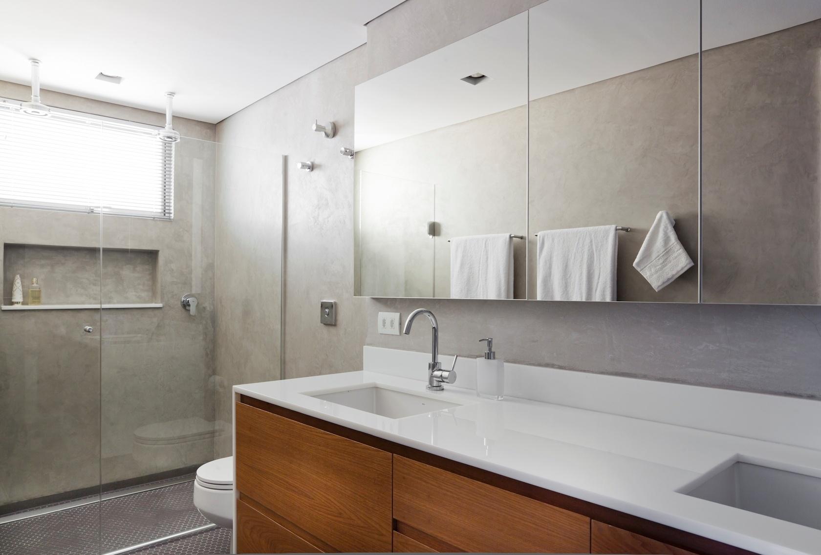A grande parede de cimento queimado recebeu armários revestidos de espelhos, em projeto definido por Renato Dalla Marta, do AUM Arquitetos, para o banheiro do casal do apartamento no Paraíso, zona sul de São Paulo. O espaço conta com gabinete em madeira freijó e tampo de massa sintética de vidro, com duas cubas