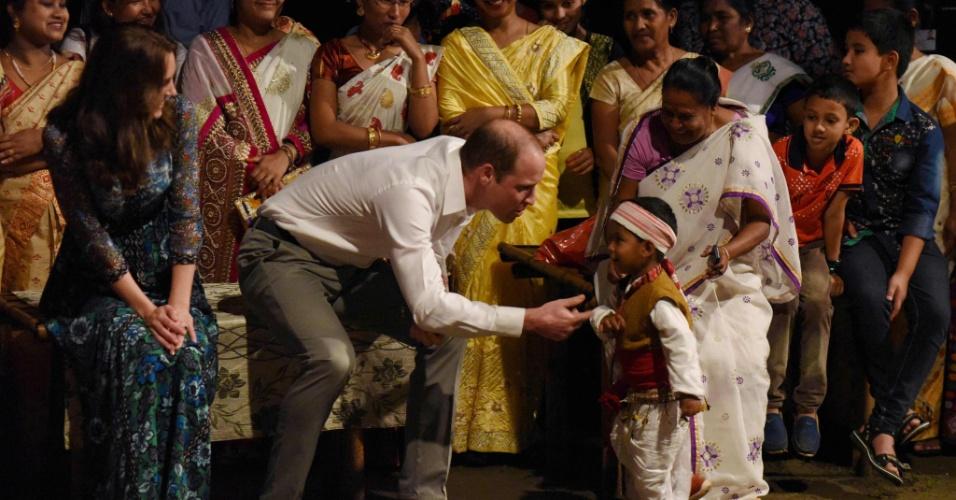 12.abr.2016 - Ao lado de Kate Middleton, príncipe William brinca com criança após assistir a apresentação da dança tradicional Bihu no parque nacional de Kaziranga, na Índia