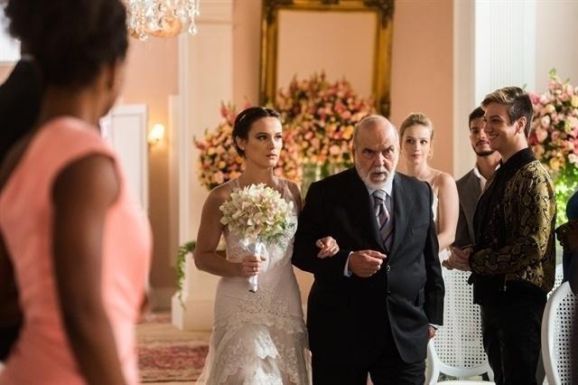 Com a fisionomia séria, Clara entra com o avô Josafá (Lima Duarte) na cerimônia do seu casamento com Renato (Rafael Cardoso)