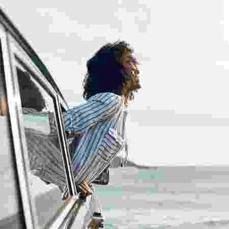 Mulher feliz para fora de carro - Getty Images