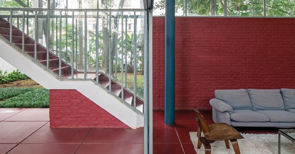 A porta de correr envidraçada permite a integração do interior com o exterior. O piso, a parede e o embasamento da escada têm a mesma cor avermelhada que contrasta com o azul acinzentado da coluna. A Casa do Arquiteto foi projetada pelo arquiteto João Batista Vilanova Artigas, em 1949
