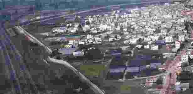 Um muro separa a cidade palestina de Qalqilia (à direita da barreira) de Israel (à esquerda)  - Creative Commons - Creative Commons