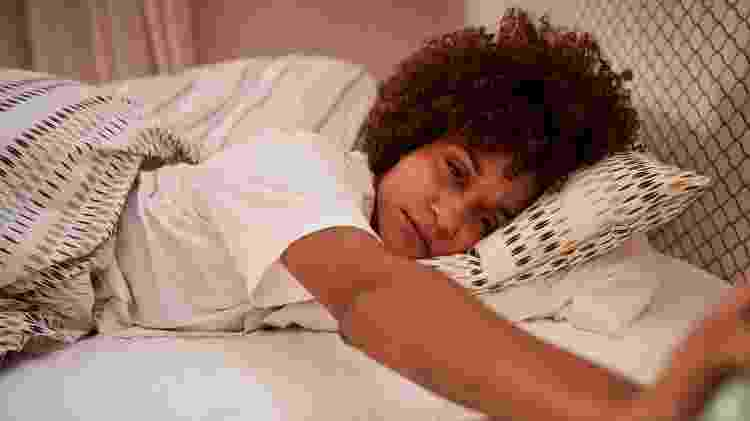 Jovem mulher com sono, deitada, insônia, na cama, dormindo - iStock - iStock