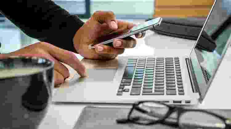 Homem usa celular e computador no home office - Getty Images/iStockphoto - Getty Images/iStockphoto