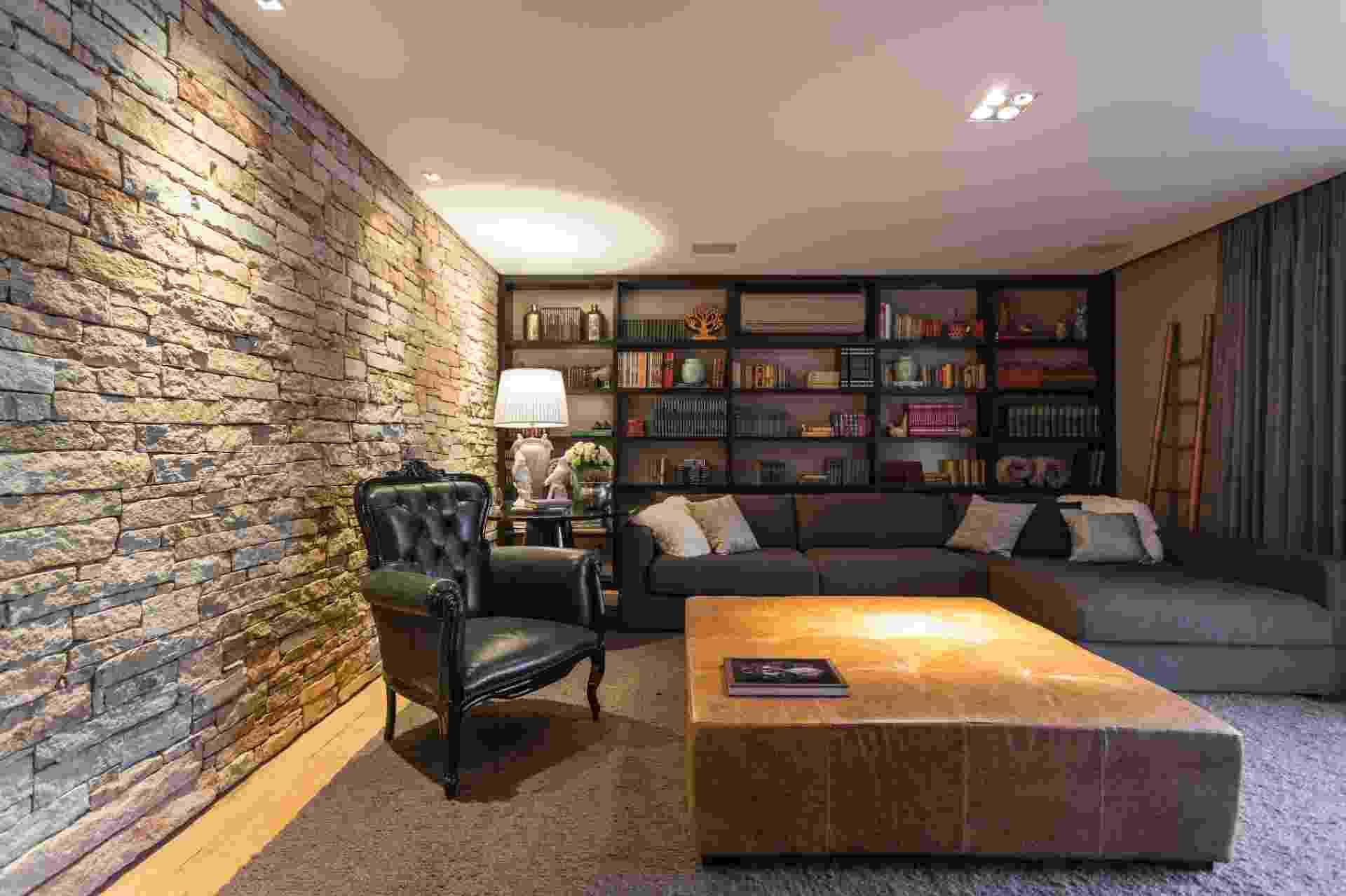 """Este canto de leitura está localizado na sala de uma casa de veraneio. O projeto do arquiteto Maurício Karan recebeu uma estante no tamanho da parede para comportar todos os livros da família. Um dos destaques é o aconchego dado pela o """"escurinho"""" do ambiente que reúne tons de marrom, preto e cinza, além da poltrona da Linfor Móveis e da luminária da L'oeil - Divulgação"""