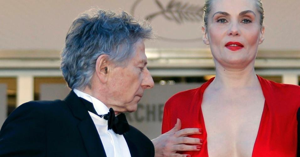 25.mai.2013 - Roman Polanski confere o decote da mulher, a atriz Emmanuelle Seigner, antes da  exibição do filme