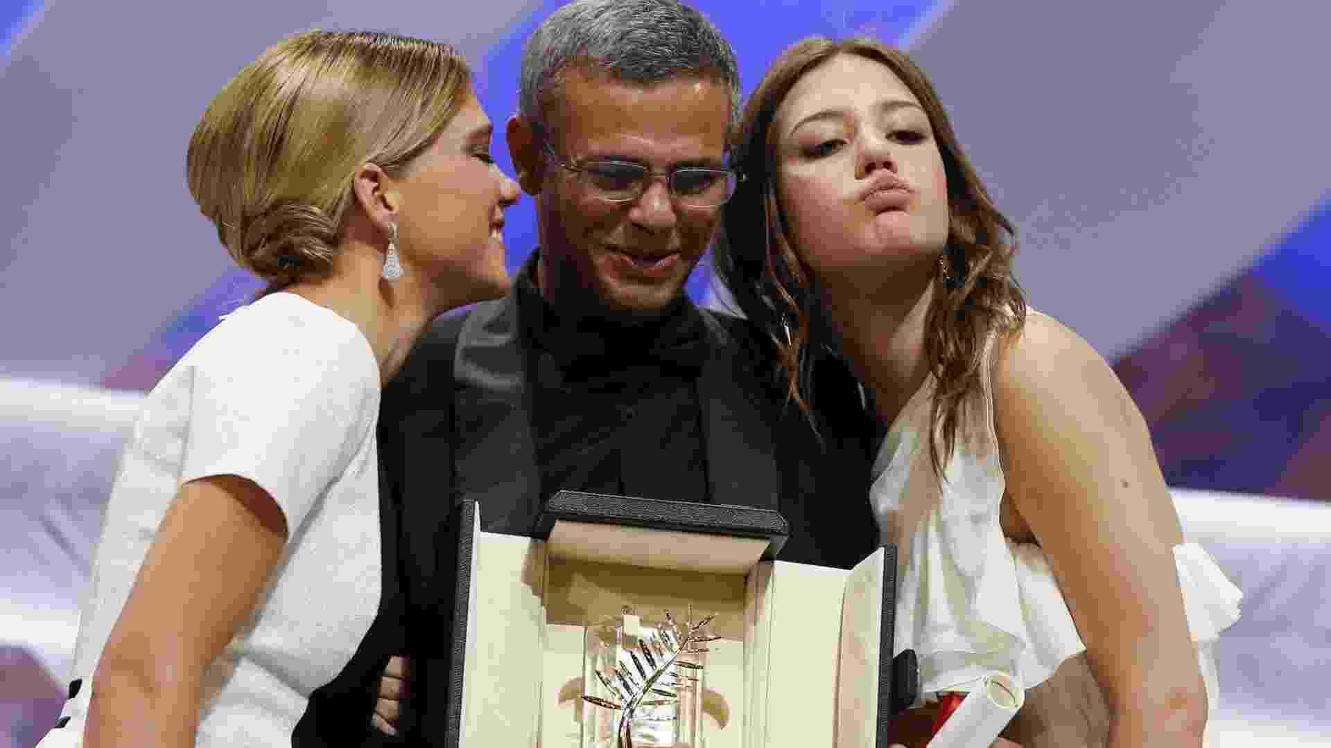 """26.mai.2013 - As atrizes francesas Lea Seydoux (à esq) e Adele Exarchopoulos abraçam o diretor franco-tunísio Abdellatif Kechiche enquanto ele recebe a Palma de Ouro pelo filme """"La Vie d'Adele"""", durante o encerramento do Festival de Cannes - Valery Hache/AFP"""