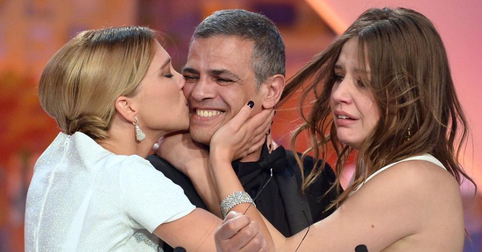 26.mai.2013 - As atrizes francesas Lea Seydoux (à esq) e Adele Exarchopoulos abraçam o diretor franco-tunísio Abdellatif Kechiche enquanto ele recebe a Palma de Ouro pelo filme