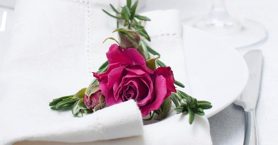 Rosas em tom de rosa bem escuro formam belo e elegante contraste com a mesa em branco