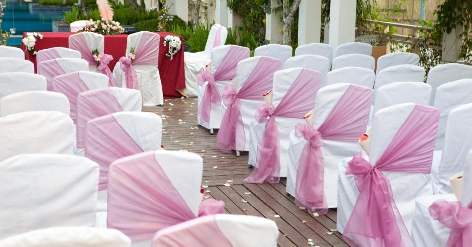 Cerimônia ao ar livre em branco e tecido rosa queimado (ou rosa antigo) enfeitando as cadeiras