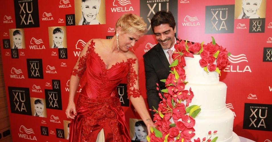 28.mai 2013- Xuxa fica encantada com o desenho do bolo e mostra os detalhes para o namorado Junno
