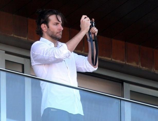 28.mai.2013- Ator Bradley Cooper tira fotos da paisagem do Rio de Janeiro, da sacada do hotel Fasano em Ipanema