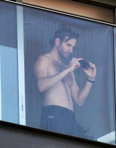 28.mai.2013- Sem camisa, ator Bradley Cooper tira fotos da paisagem do Rio de Janeiro, da sacada do hotel Fasano em Ipanema