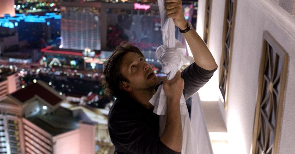 Phil (Bradley Cooper) fica pendurado em um lençol na sacada de hotem em Las Vegas