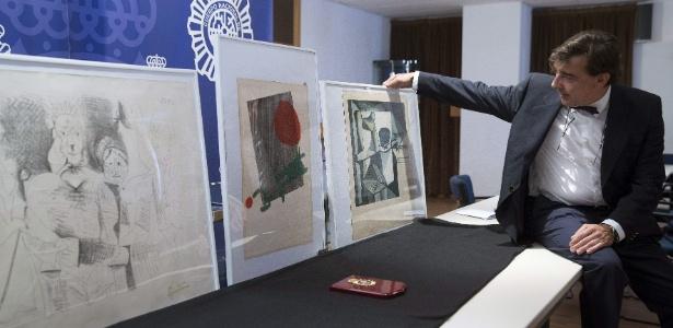 """O colecionador Guillermo Prieto, dono das gravuras """"El búho"""" e """"Portrait de Famille"""", de Picasso, e de xilografia em papel de Joan Miró, junto às obras, recuperadas pela polícia espanhola em Málaga três anos após o furto - Jorge Zapata/EFE"""