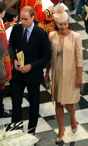 4.jun.2013 - Príncipe William e Kate Middleton deixam a catedral de Westminster para a missa em comemoração aos 60 anos da coroação da Rainha Elizabeth 2ª. A duquesa de Cambridge usou um vestido discreto e um casaco comprido, ambos da estilista britânca Jenny Packham, mas era possível ver a barriga da gravidez. Ela ainda usou um chapéu Jane Taylor, que custa US$ 1.200,00. O primeiro filho de Kate e William deve nascer no meio de julho