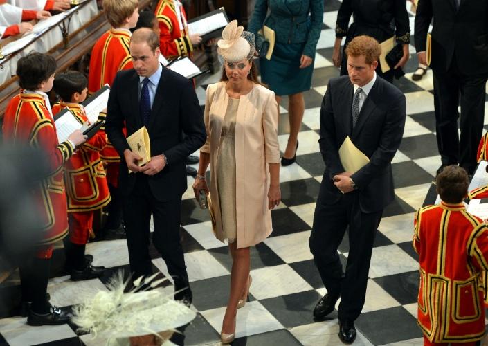 4.jun.2013 - Príncipe William, Kate Middleton e o príncipe Harry deixam a catedral de Westminster para a missa em comemoração aos 60 anos da coroação da Rainha Elizabeth 2ª. A duquesa de Cambridge usou um vestido discreto e um casaco comprido, ambos da estilista britânca Jenny Packham, mas era possível ver a barriga da gravidez. Ela ainda usou um chapéu Jane Taylor, que custa US$ 1.200,00. O primeiro filho de Kate e William deve nascer no meio de julho