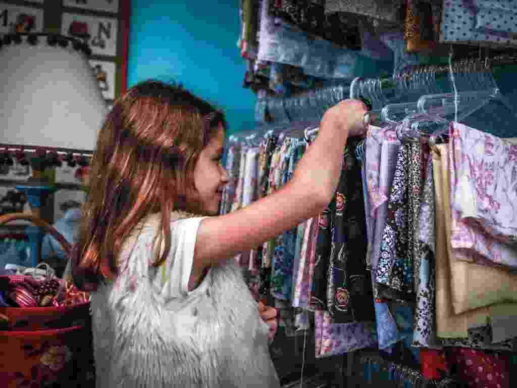 As aulas são semanais e, a cada encontro, Maria Victoria, de 9 anos, é quem decide o que deseja fazer. Em geral, ela já sai da escola levando a sua produção. Com a ajuda da professora, ela pode confeccionar peças de roupas, acessórios, brinquedos ou objetos para a decoração. Desta vez, ela decidiu costurar uma almofada e o primeiro passo é escolher os tecidos. Na arara, há diversas opções à disposição da aluna - Leandro Moraes/UOL