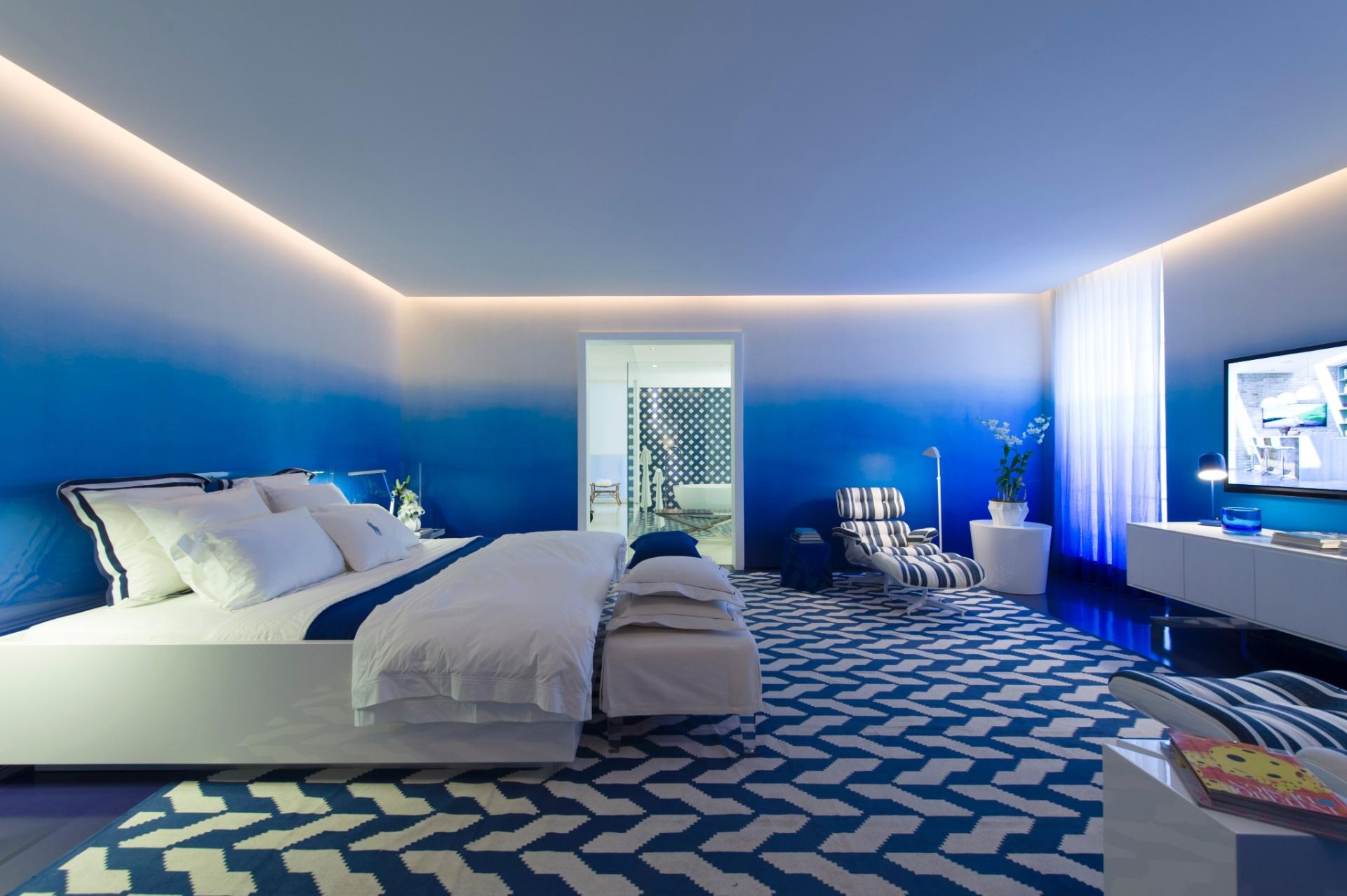 No quarto da Casa de Praia, projeto de Roberto Migotto, se destacam as tonalidades do azul nos móveis, no tapete em formas geométricas e, em especial, no degradê da parede. A 27ª Casa Cor SP segue até dia 21 de julho de 2013, no Jockey Club de São Paulo