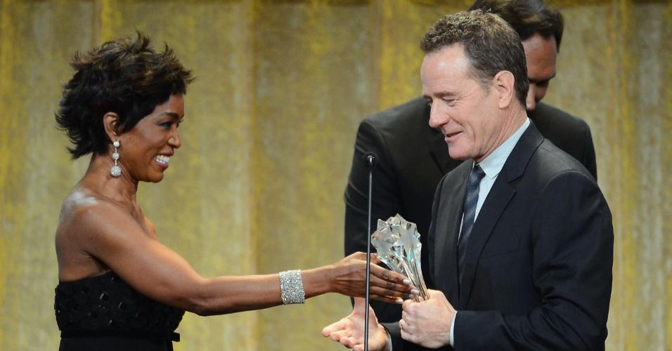 """10.jun.2013 - O ator Bryan Cranston aceita prêmio de melhor ator de série dramatica por """"Breaking Bad"""" das mãos de Angela Bassett no Critics' Choice TV awards, no Beverly Hills Hotel, em Los Angeles"""