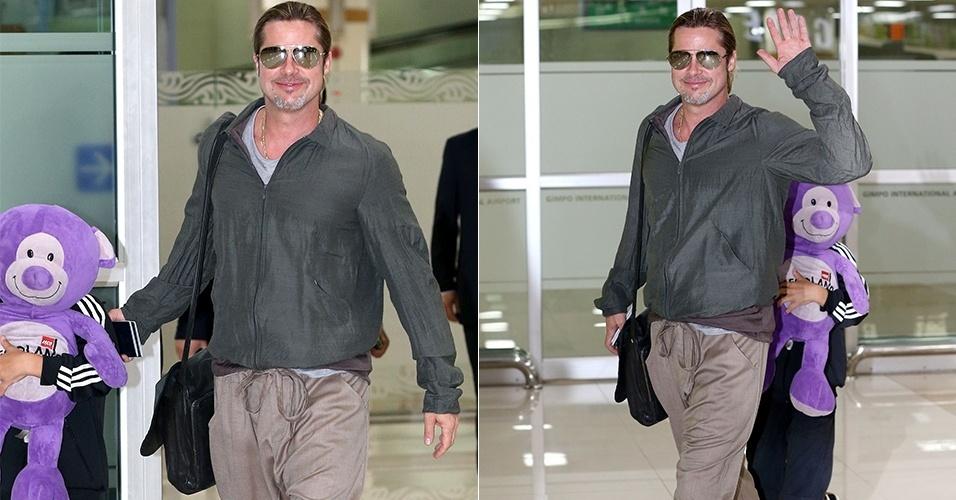 11.jun.2013 - Brad Pitt acena para os fotógrafos enquanto seu filho Pax Thien Jolie-Pitt se esconde atrás de um bicho de pelúcia roxo, ao desembarcarem no aeroporto internacional de Seul