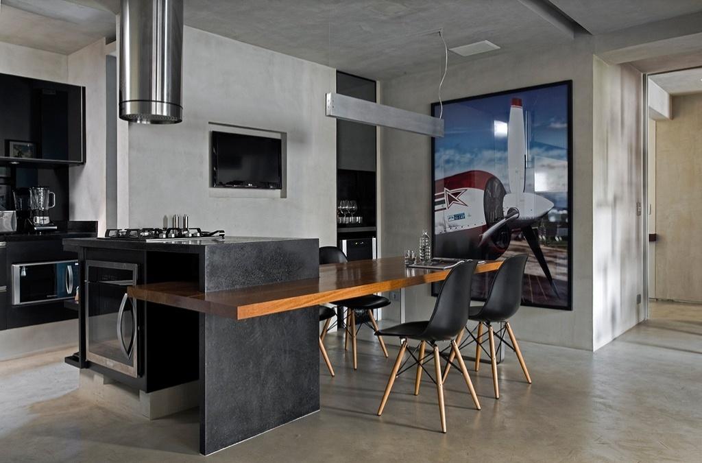 A proposta de integração total abrange também a sala de jantar e a cozinha, instaladas no local do antigo quarto de empregada. Na lateral direita, o pequeno nicho foi aproveitado para a instalação da adega. Na parede, foto de avião, hobby do proprietário. Sobre a mesa, a luminária pendente em aço escovado é da La Lampe. O projeto de reforma do Loft Real Park é do arquiteto Diego Revollo