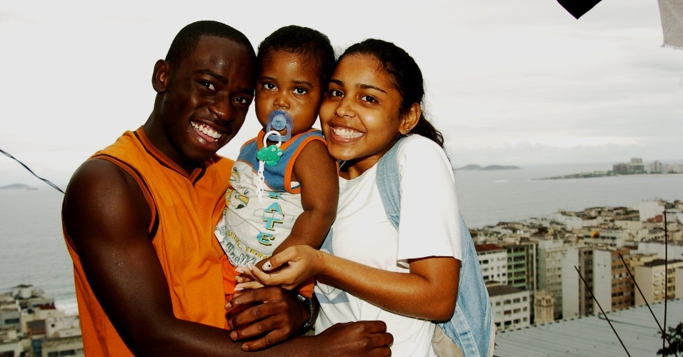 """Acerola (Douglas Silva), Cristiane (Camila Monteiro) e o filho deles na série """"Cidade dos Homens"""", série que ficou no ar na Globo durante 2002 e 2005"""