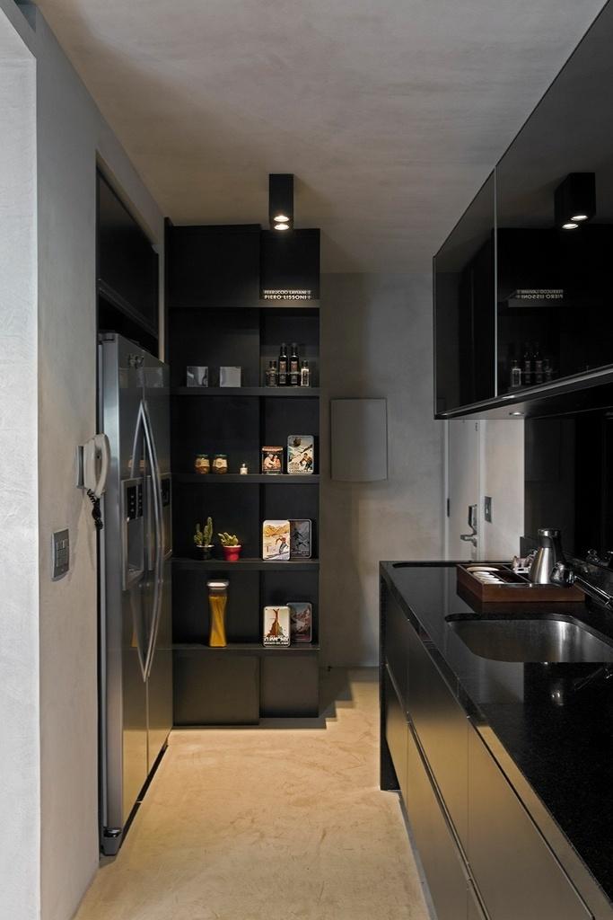 Em preto e cinza, a pequena cozinha tem móveis planejados da Artigiano e segue o estilo sóbrio e contemporâneo restante do Loft Real Park, cuja reforma foi projetada pelo arquiteto Diego Revollo