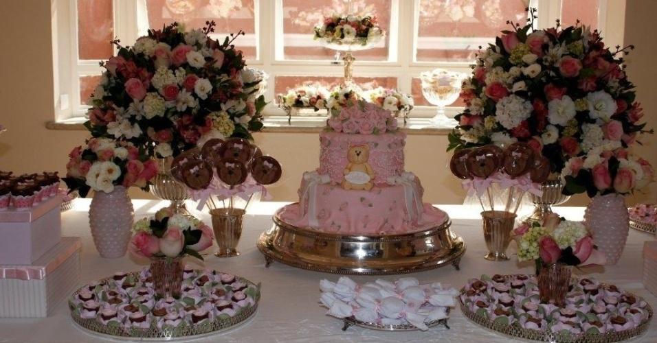 Neste chá de apresentação, a mesa de doces e bolo foi o grande destaque da decoração, feita por Deborah Doll. Buquês de diferentes tipos de flores em tons claros, dispostos sobre a mesa e próximos às janelas, foram o suficiente para que a ambientação ficasse muito mais sofisticada