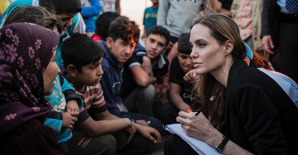 18.jun.2013 - Enviada especial do Alto Comissariado da ONU para os refugiados, a atriz Angelina Jolie fala com refugiados sírios no campo militar da Jordânia perto da fronteira entre os dois países