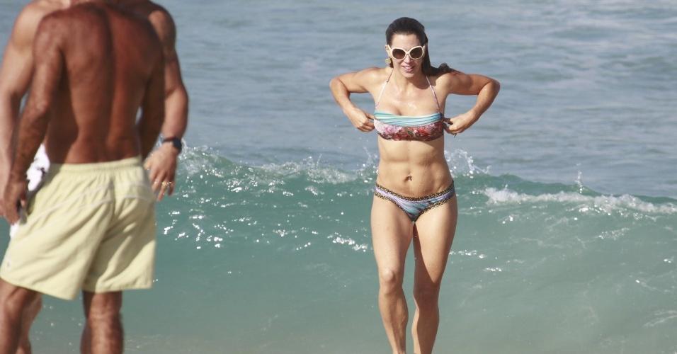 19.jun.2013 - Joana Prado se refresca na praia da Barra da Tijuca, no Rio de Janeiro. A apresentadora está acompanhada do marido, o lutador Vitor Belfort