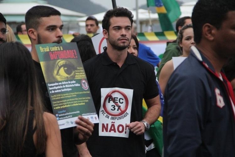 23.jun.2013 - O ator Sidney Sampaio leva cartaz contra a PEC 37 durante manifestação na orla de Copacabana, no Rio de Janeiro