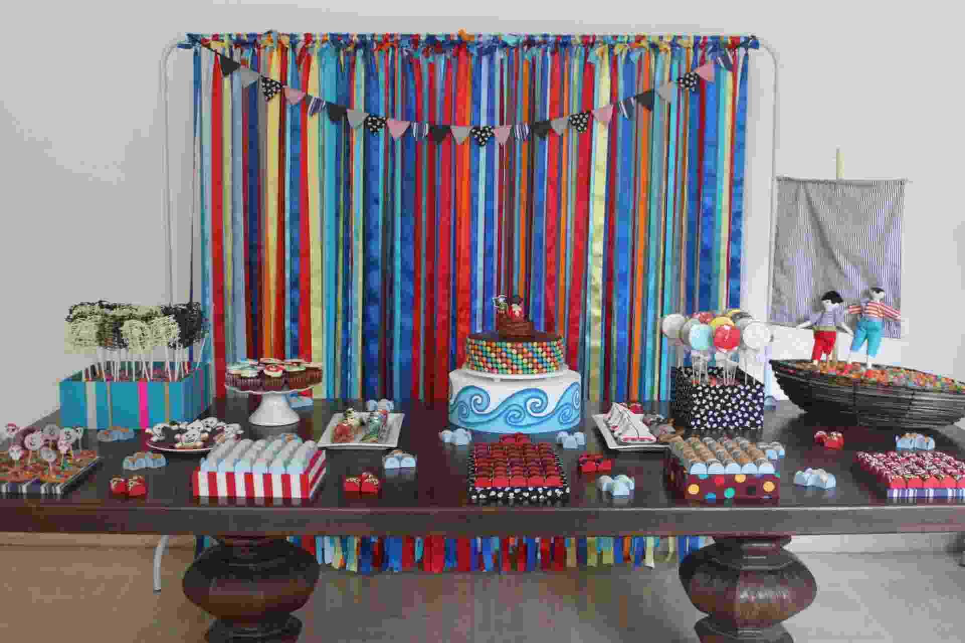 A festa realizada por Tammy Montagna (www.tammymontagna.com) tem o tema Pirata. A cortina que cobre a janela do salão de festas foi feita exclusivamente para a comemoração, com uma estrutura de ferro onde foram presas fitas coloridas de cetim - Divulgação