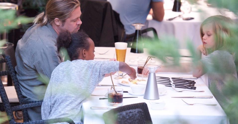 """Brad Pitt janta com as filhas Zahara (esq.) e Shiloh (dir.) em um restaurante em Madri, Espanha. O ator, que cancelou sua visita ao Rio de Janeiro por causa das manifestações nas ruas, mudou sua programação e está na Europa fazendo a divulgação do filme """"Guerra Mundial Z"""""""
