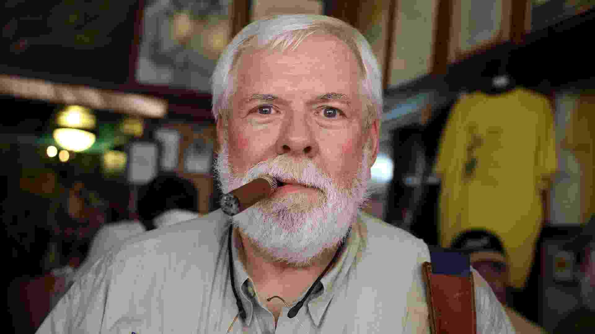 21.jun.2013 - Um dos sósias de Hemingway posa fumando um charuto no La Bodeguita del Medio, um dos locais preferidos do escritor em Havana - Alejandro Ernesto/EFE